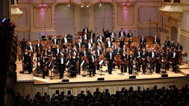 Applausszene: Thomas Hengelbrock und das NDR Sinfonieorchester stehen auf der Bühne der Laeiszhalle. © NDR Fotograf: Marcus Krueger
