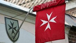 Eine Fahne mit dem weißen Malteser-Kreuz auf rotem Grund hängt an einem Gebäude. © dpa picture alliance Foto: Ralph Goldmann