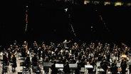 Dirigent und Musiker beim Schlussapplaus vor den dunklen Rängen des Zuschauerraums © NDR Fotograf: Marco Maas