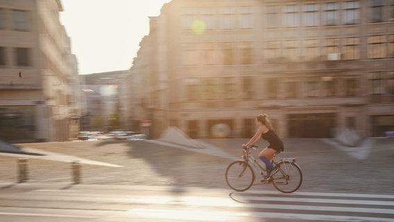 Eine Frau fährt mit einem Fahrrad auf der Straße © Picture Alliance | Photoshot Foto: Picture Alliance / Photoshot