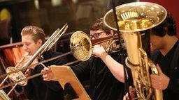 Drei junge Männer spielen Posaune und Tuba. © NDR