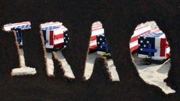Blick durch ein Metallschild auf die Särge der im Irak getöteten US-Soldaten in Santa Monica © dpa - Report