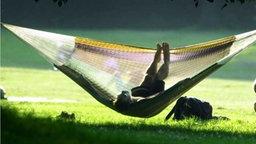 Frau schaukelt in einer Hängematte in einem Park. © Picture-Alliance/dpa