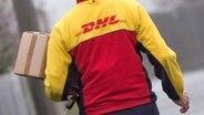 Ein Zusteller von DHL trägt ein Paket. © dpa - Bildfunk Fotograf: Daniel Karmann/dpa