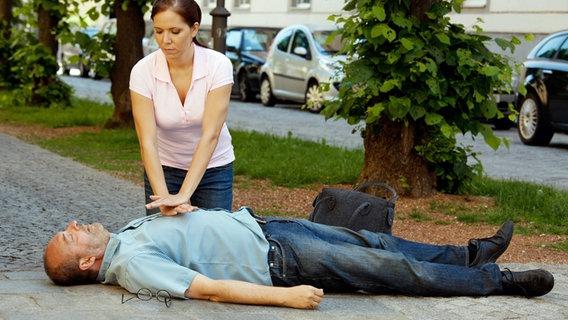 امرأة تقدم الإسعافات الأولية لرجل أصيب بنوبة قلبية في الشارع.