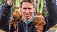 Gartenprofi Peter Rasch holds two Amaryllis-Zwiebeln. © NDR