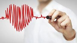 Ein Mann, der im Hintergrund unscharf zu erkennen ist, mit weißem Hemd, zeichnet auf eine Glasscheibe ein Herz aus Kurven. © fotolia.com Foto: peshkov