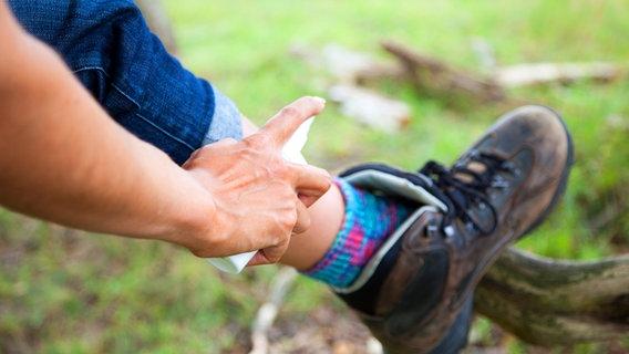 Una mujer se rocía repelente de mosquitos en la pierna.  © Picture-Alliance / dpa Themendienst Fotografía: Christine Klose