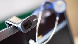 An einem Computerbildschirm mit Webcam hängt ein Strethoskop © picture-alliance/dpa Foto: Monika Skolimowska