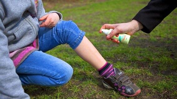 Se rocía un aerosol repelente de garrapatas en la pierna de la niña.  © Picture-Alliance / dpa Themendienst Fotografía: Sylvia Marx