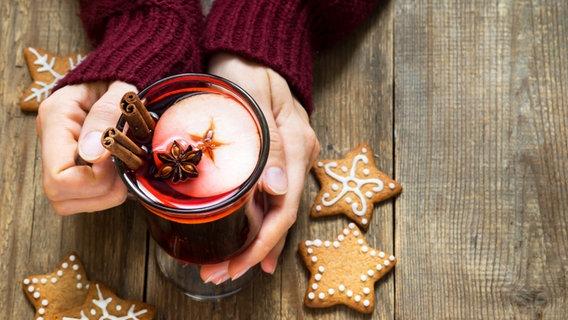 Eine Frau sitzt am Tisch und hält ein Glas Glühwein in den Händen, daneben liegen ein paar Weihnachtskekse. © Colourbox Foto: -