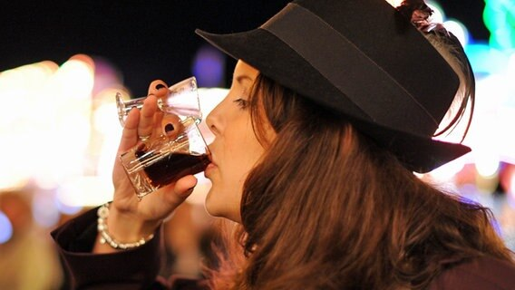 Eine junge Frau trinkt parallel ein Glas Korn und ein Glas dunkles Bier. © dpa Foto: Julian Stratenschulte