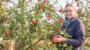 Kerstin Hintz steht auf ihrem Bauernhof im Alten Land vor einem Apfelbaum voller Früchte. © NDR Foto: Claudia Timmann