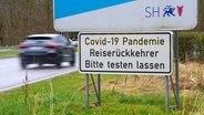 Ein Warnschild an der deutsch-dänischen Grenze weist Reiserückkehrer auf Testpflich hin. © Picture-Alliance / Jörg Carstensen
