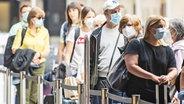 Passagiere mit Atemschutzmasken stehen in einer Warteschlange am Flughafen in Zürich. © Keystone / picture alliance Foto: Enno Leanza