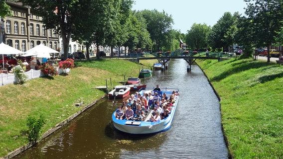Ein Boot mit Touristen fährt in Friedrichstadt auf einer Gracht. © NDR Foto: Kathrin Weber