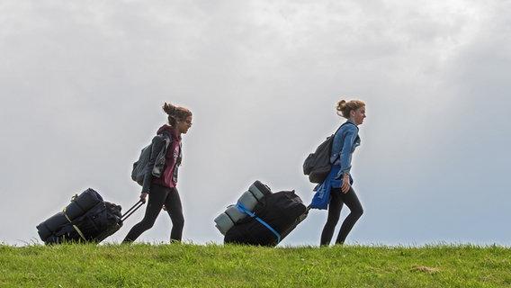 Zwei junge Mädchen gehen mit Gepäck auf einem Deich entlang. © picture alliance Foto: Ingo Wagner