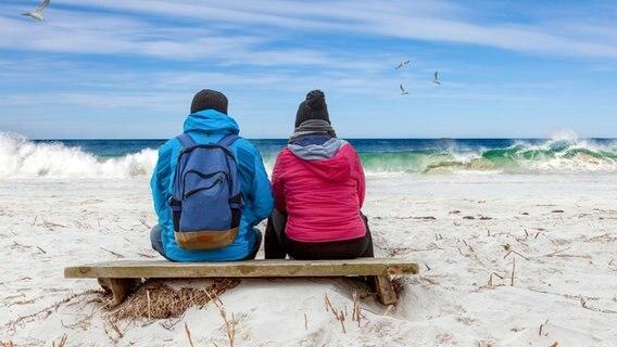 Un couple en veste chaude et sac à dos est assis sur la plage et regarde la mer. © photocase.de Photo : Nordreisender