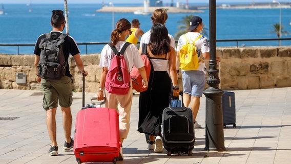 Touristen gehen mit Rollkoffern durch Palma de Mallorca. © dpa-Bildfunk Foto: Clara Margais
