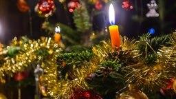 Ein geschmückter Weihnachtsbaum mit echten brennenden Kerzen. © Colourbox Foto: alho007