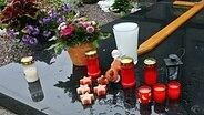 Grablichter in Kunststoffhüllen auf einer Grabstätte © imago/xcitexpress