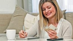 Eine Frau mit Notizblock beim Geldzählen. © Christian Klose
