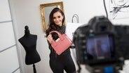 Eine junge Frau präsentiert vor der Kamera eine Handtasche. © picture alliance / dpa Themendienst Foto: Christin Klose