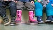 Kindergartenkinder sitzen mit Gummistiefeln auf einer Bank im Raum und warten. © picture alliance Foto: Ralf Hirschberger