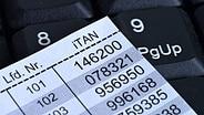 Eine TAN-Liste auf Papier liegt auf einer Tastatur. © imago/Schöning
