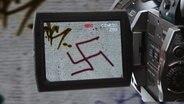 Ein Hakenkreuz-Gaffitti in einem Kameradisplay. (Montage) © NDR, fotolia Fotograf: Christine Raczka, nikkytok