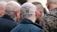 Tätowierte Glatzen von Skinheads bei einer NPD-Demonstration. © Imago Foto: momentphoto/Killig