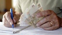 Ein Rentnersitzt an einem Tisch und macht sich auf einem Block diverse Notizen seiner Geldausgaben, in der anderen Hand hält er verschiedene Euro-Geldscheine. © picture-alliance/ dpa Fotograf: Andreas Gebert