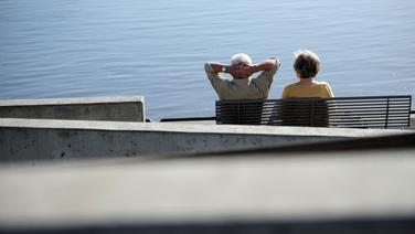 Ein Senionen-Paar sitzt an der Elbe auf einer Bank. © dpa Foto: Christian Charisius