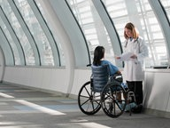 Eine Ärztin mit einer Frau im Rollstuhl