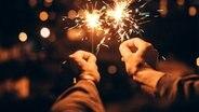 Zwei Hände halten zwei Wunderkerzen im Dunkeln. © photocase Foto: criene