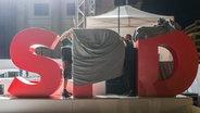 Die Buchstaben SPD auf einer Bühne werden zugedeckt. © picture alliance / NurPhoto Foto: Omer Messinger