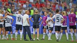 Spielerinnen der deutschen Fußball-Nationalmannschaft der Frauen und die Trainerin Martina Voss-Tecklenburg (M.) stehen nach einem Spiel zusammen auf dem Rasen. © dpa picture alliance/NurPhoto Foto: Jose Breton