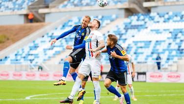 Rostocks Jan Löhmannsröben (M.) kämpft gegen Saarbrückens Tim Golley (l.) und Mario Müller um den Ball.   imago images / Eibner