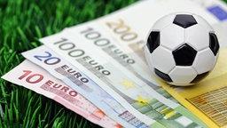 Ein Fußball auf Geldscheinen. © picture alliance/Bildagentur-online