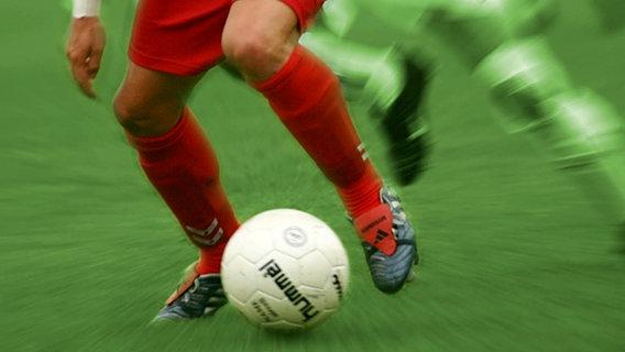 Fußballer mit roten Stutzen im Begriff den Ball zu spielen © panthermedia / Klosko Foto: Robert Klosko