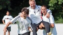 DFB-Trainer Horst Hrubesch wird von Mats Humnmels (l.) und Sandro Wagner auf Händen getragen. © dpa