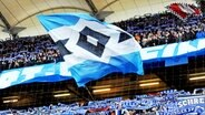 HSV-Fans im Volksparkstadion schwenken eine große Fahne. © Witters Foto: Frank Peters