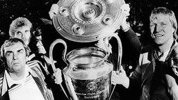 HSV-Trainer Ernst Happel (l.) und seine Spieler Thomas von Heesen (l.o.) und Horst Hrubesch (r.) mit der Meisterschale und dem Europacup der Landesmeister. © dpa - Sportreport