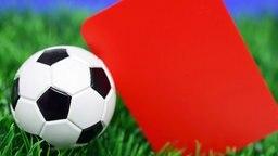 Ein Fußball liegt neben einer Roten Karte © picture alliance