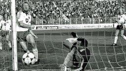HSV-Stürmer Horst Hrubesch trifft am 16.10.1982 in der zweiten Runde des DFB-Pokals im Spiel gegen Werder Bremen zum 1:1-Ausgleich gegen Torwart Dieter Burdenski. © picture-alliance / dpa