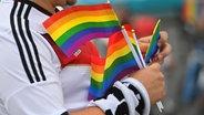 Ein Mann hält kleine Regenbogenflaggen in der Hand © picture alliance / SvenSimon   Frank Hoermann/SVEN SIMON