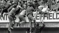 Von den überfüllten unteren Traversen im Hillsborough-Stadion versuchen Zuschauer verzweifelt, sich auf den Rang hochzuziehen.