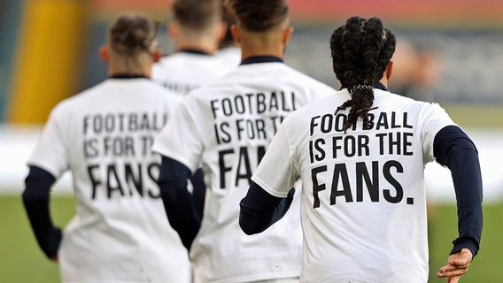 "Leeds-United-Spieler mit T-Shirts mit der Aufschrift ""Football is for the Fans"" © IMAGO / PA Images"