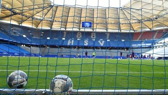 Im leeren Volksparkstadion in Hamburg liegen zwei Bälle im Tornetz. © Witters Foto: Valeria Witters