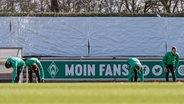 Die Werder-Profis Theodor Gebre Selassie, Yuya Osako, Ludwig Augustinsson und Niklas Moisander (v.l.) dehnen sich auf dem Trainingsplatz. © imago images / foto2press